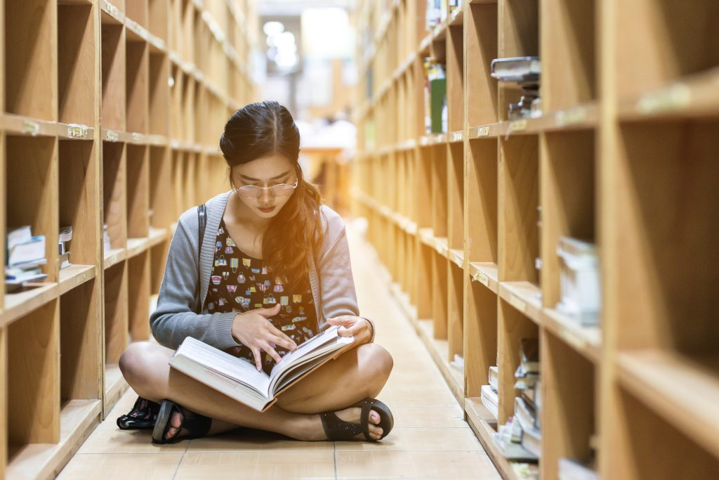 A student sitting on a library floor, reading a book